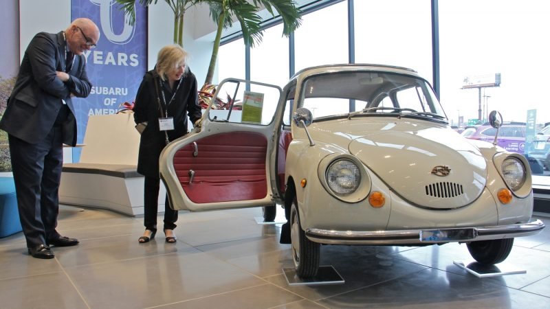 Guests J. J. Broderick and Eileen Stilwell check out a vintage Subaru 360, the company's first automobile, during the grand opening of Subaru of America's headquarters in Camden. (Emma Lee/WHYY)