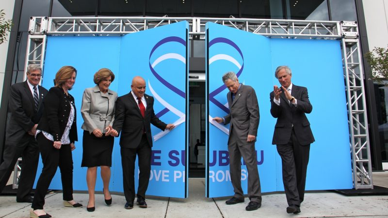 Subaru of America President Tom Doll (second from right) and Camden Mayor Frank Moran open the doors to the new Subaru headquarters in Camden. (Emma Lee/WHYY)