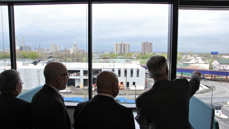 Subaru of America President Tom Doll (right) shows off the view from the new headquarters, which includes a look at the 107,000-square-foot national service training center expected to open by late summer. (Emma Lee/WHYY)
