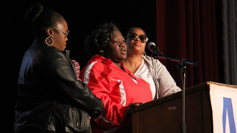 Gratz school parent leader Monica Haynesworth (center) talks about the shooting death of her 16-year-old son in 2014. She is flanked by two women who also lost sons to gun violence. (Emma Lee/WHYY)