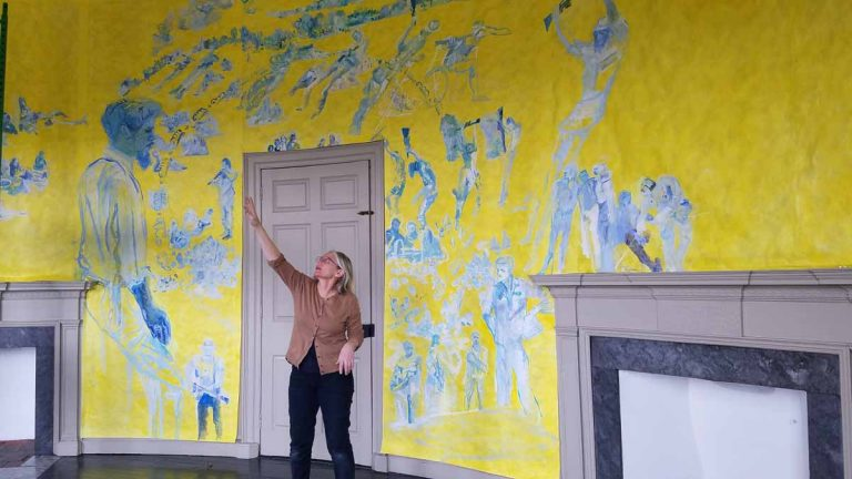 Artist Jane Irish explains how she painted one of the oval rooms in the Lemon Hill mansion to depict an anti-war demonstration that took place in Valley Forge, in 1970. (Peter Crimmins/WHYY)