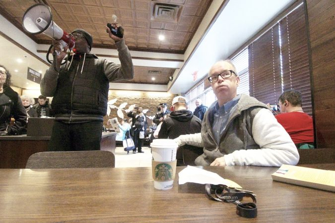 People gather inside a Starbucks on 18th and Spruce streets in Philadelphia to protest Thursday's controversial arrest. (Bastiaan Slabbers for WHYY)