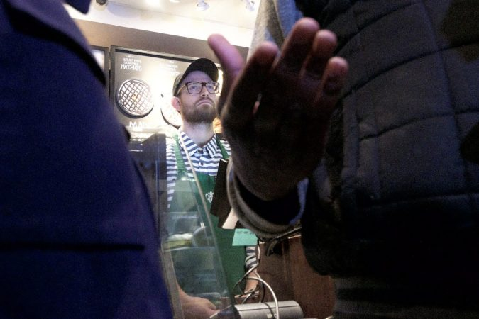 A Starbucks employee looks on as Asa Khalif speaks to people gathered inside a Starbucks on 18th and Spruce streets in Philadelphia to protest Thursday's controversial arrests of two black men. (Bastiaan Slabbers/for WHYY)