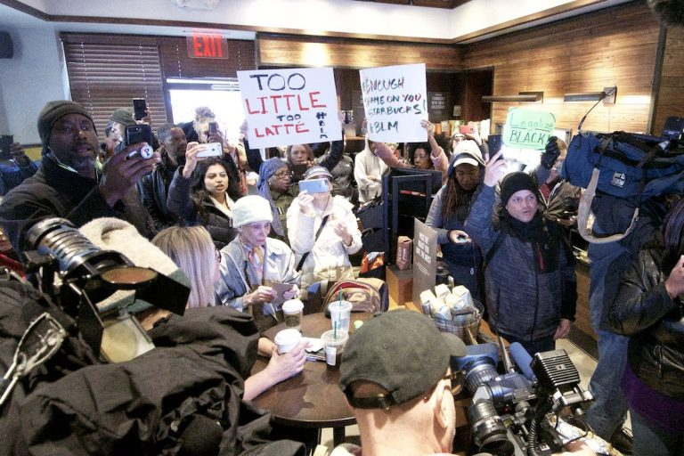People gather at a Starbucks on 18th and Spruce streets in Philadelphia to protest Thursday's controversial arrests of two black men at the store. (Bastiaan Slabbers/for WHYY)
