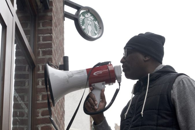 Asa Khalif of Black Lives Matter uses a bullhorn during an April protest at Starbucks in Center City Philadelphia. (Bastiaan Slabbers/for WHYY)