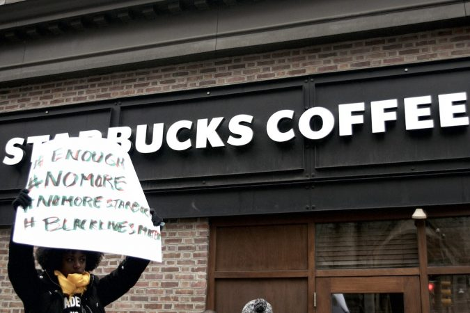 People gather outside a Starbucks on 18th and Spruce streets in Philadelphia to protest Thursday's controversial arrests of two black men at the store. (Bastiaan Slabbers/for WHYY)