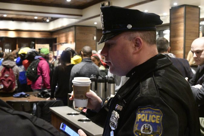 A police officer sips from a cup of coffee inside the Starbucks on 18th and Spruce streets on Monday Morning. (Bastiaan Slabbers for WHYY)