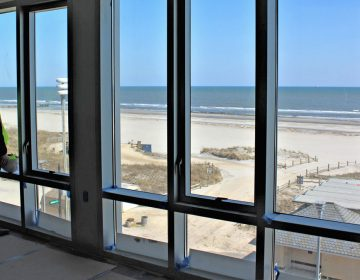 Stockton's director of operations; Alex Marino looks out at the Atlantic Ocean. He is standing inside what will be the common area for one of Stockton's four bedroom suites.   (Bill Barlow/for WHYY)