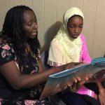 Aminata Sy reading to Dieynaba, an eighth-grader from Senegal who recently came to the U.S. (Photo courtesy of Aminata Sy)