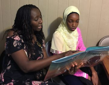 Aminata Sy reading to Dieynaba, an eighth-grader from Senegal who recently came to the U.S. (Photo courtesy of Aminata Sy)