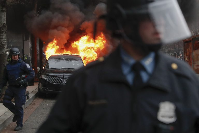 A parked limousine burns as riot police clear the street during a demonstration after the inauguration of President Donald Trump, Friday, Jan. 20, 2017, in downtown Washington. Protesters registered their rage against the new president Friday in a chaotic confrontation with police who used pepper spray and stun grenades in a melee just blocks from Donald Trump's inaugural parade route. Scores were arrested for trashing property and attacking officers.  (AP Photo/John Minchillo)