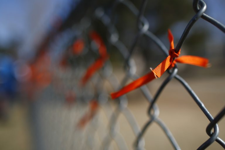A orange ribbons adorns a fence after it was put there by a student during a walkout to protest gun violence on the soccer field behind Columbine High School Wednesday, March 14, 2018, in Littleton, Colo. More than 250 students took part in the short protest at Columbine, the scene of a mass school shooting on April 20, 1999. (David Zalubowski/AP Photo)