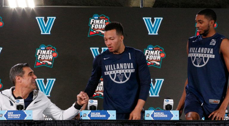 Villanova head coach Jay Wright, left, offers to bump his fist as Jalen Brunson and Mikal Bridges arrive at a news conference for the championship game of the Final Four NCAA college basketball tournament, Sunday, April 1, 2018, in San Antonio. (AP Photo/Brynn Anderson)