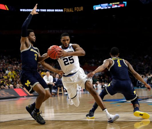 Villanova guard Mikal Bridges (25) drives to the basket between Michigan's Zavier Simpson, left, and Charles Matthews, right, during the second half in the championship game of the Final Four NCAA college basketball tournament, Monday, April 2, 2018, in San Antonio. (AP Photo/David J. Phillip)