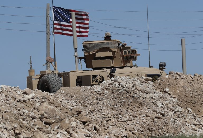 A U.S. soldier sits on an armored vehicle behind a sand barrier at a newly installed position near the tense front line between the U.S-backed Syrian Manbij Military Council and the Turkish-backed fighters, in Manbij, north Syria, Wednesday, April 4, 2018. A week ago, there was just a single house where U.S. soldiers had hoisted a U.S. flag on a hill a little ways back from a tense front line in Syria. Now on Wednesday stood a growing outpost with a perimeter of large sand barriers and barbed wire, a new watch tower and half a dozen armored vehicles, The Associated Press found. (Hussein Malla/AP Photo)