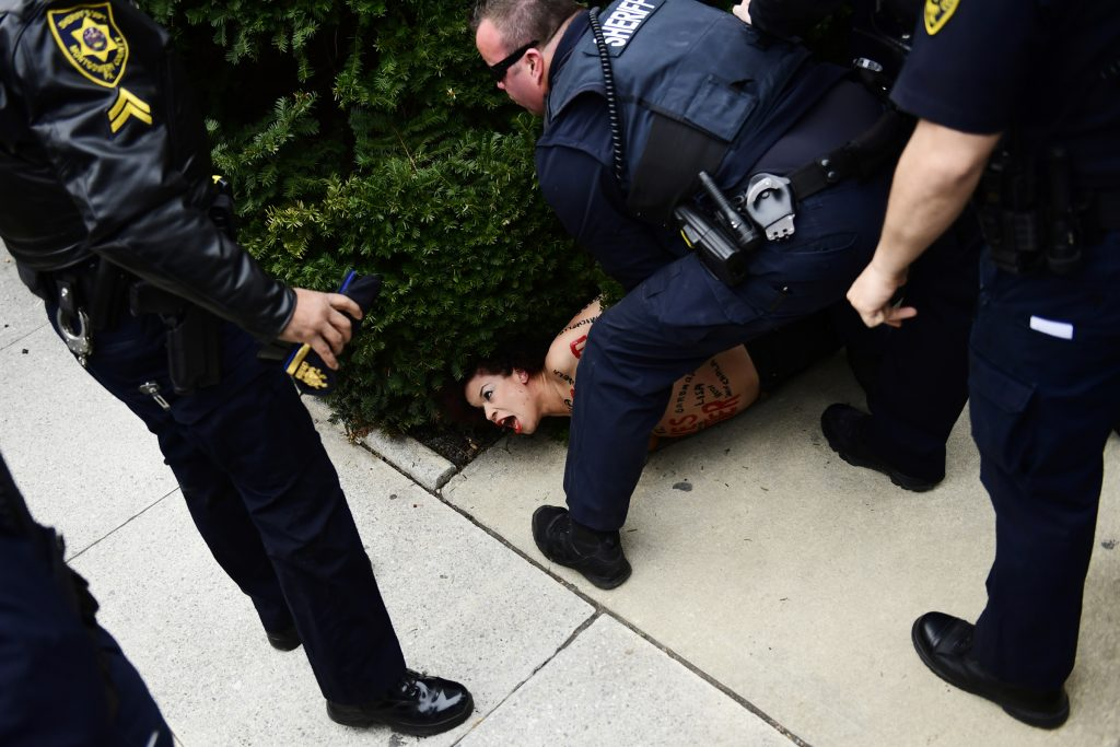 A protester is detained as Bill Cosby arrives for his sexual assault trial at the Montgomery County Courthouse, Monday, April 9, 2018, in Norristown, Pa.