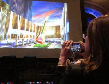 This April 18, 2018 photo shows a media member taking photos of a video presentation about the new Hard Rock casino during a press conference in New York at which the company announced its Atlantic City casino will open on June 28. (Wayne Parry/AP Photo)