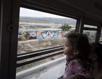 A Central American child who is traveling with a caravan of migrants, peers at the border wall from a bus carrying the group to a gathering of migrants living on both sides of the border, in Tijuana, Mexico, on April 29. (AP Photo/Hans-Maximo Musielik)
