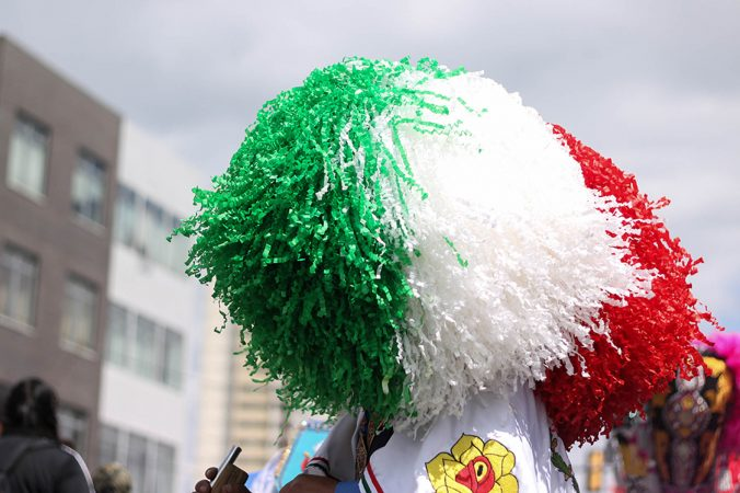 Carnavaleros celebrate in bearded masks and embroidered  Suits, draping themselves in the colors of the Mexican  flag.  (Angela Gervasi for WHYY)