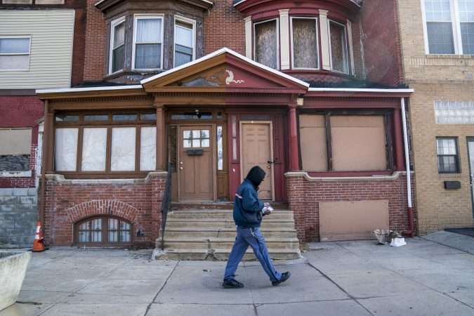 A man walks down a residential street in Strawberry Mansion. (Jessica Kourkounis/WHYY)