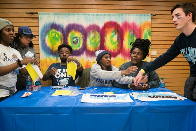 Villanova students Opeyemi Famakinwa, Nkiambi Sokolo, Takiyah Bethea and Ijeoma Ezengwa pass out wristbands to fellow students at the Connelly Center before the NCAA men's basketball championship game. (Branden Eastwood for WHYY)