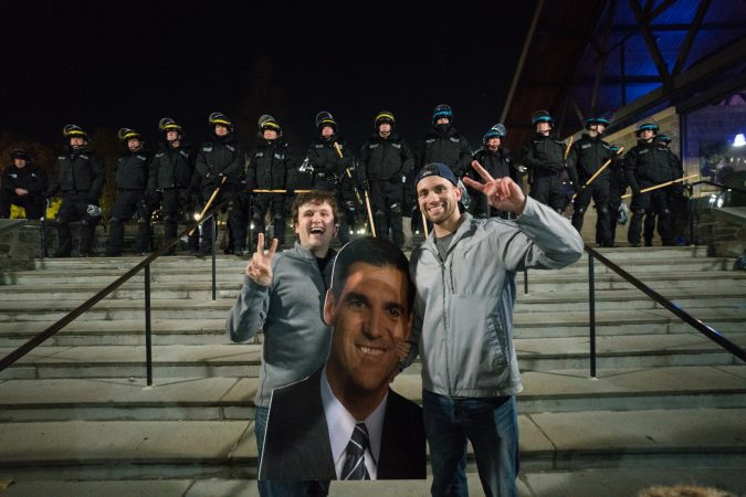 Villanova alums Patrick Frangos, on left, and Mike Arpa pose for a photo in front of riot police with a cut out head of the men's basketball team coach Jay Wright. (Branden Eastwood for WHYY)