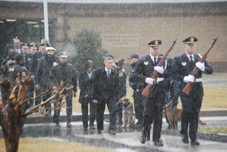 Delaware is offering $3,000 signing bonuses to new correctional officers. In this photo, Gov. John Carney (center, in dark suit) attends a memorial service for Lt. Steven Floyd, who was killed during an uprising by prison inmates in February 2017. (John Jankowski/for WHYY)