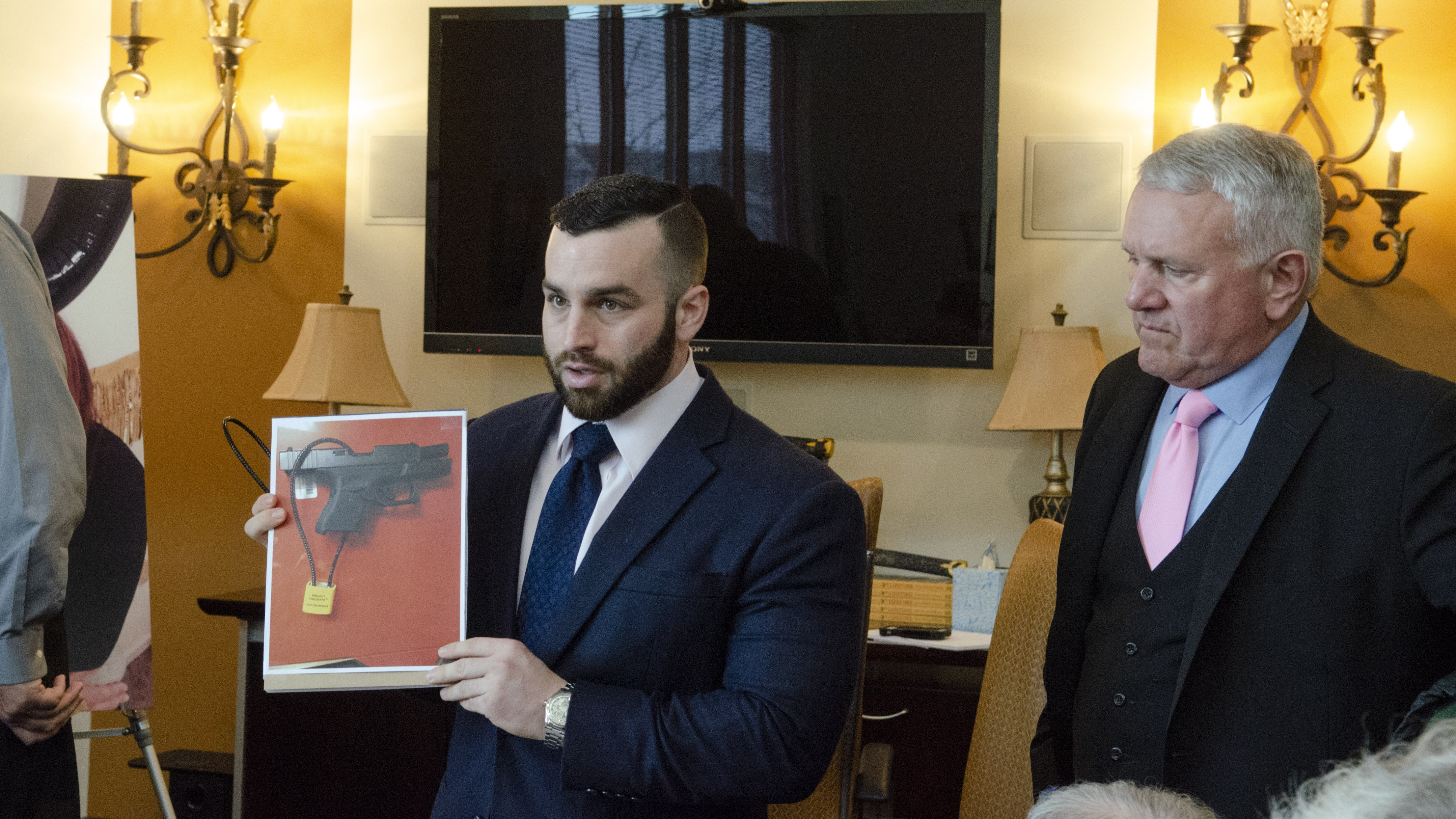 Attorney Oliver Barry shows a photo of a gun lock that might have saved Kelly Ann McDowell's life, as attorney Paul D'Amato looks on.