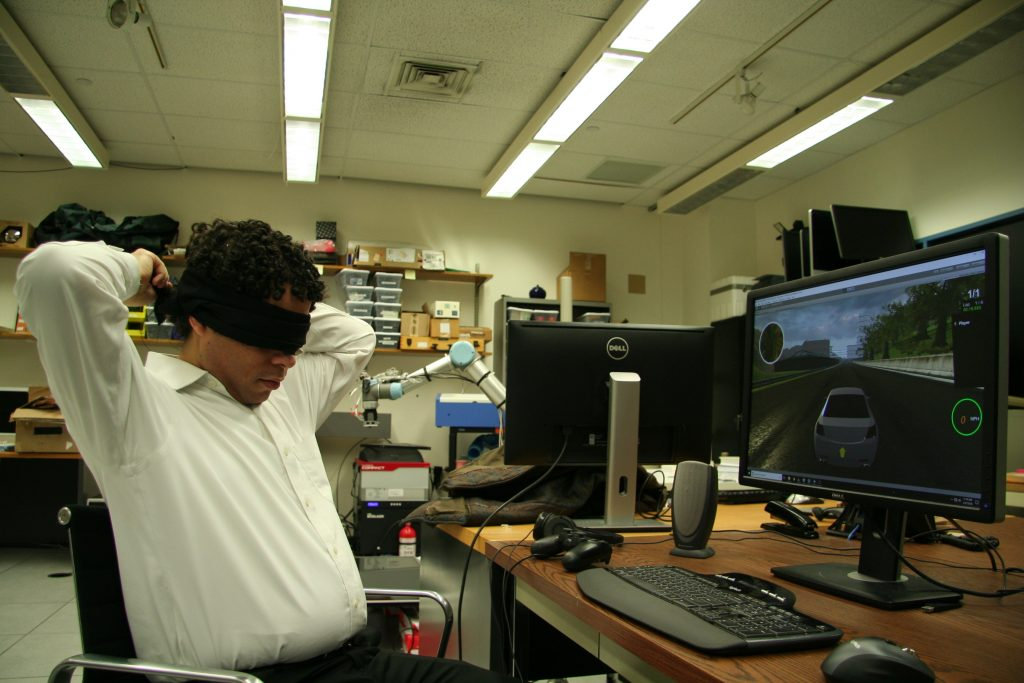 Brian Smith ties a strip of light absorbing blackout cloth around his eyes as a blindfold. He made a user interface so blind players can play racing games, and tested it with blind volunteers, and blindfolded sighted volunteers.