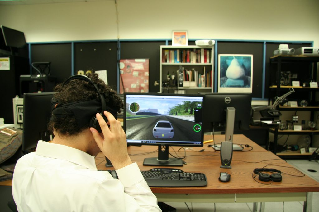 Brian Smith puts on a pair of headphones to play his racing game. He made a user interface so blind players can drive in video games just like sighted players.