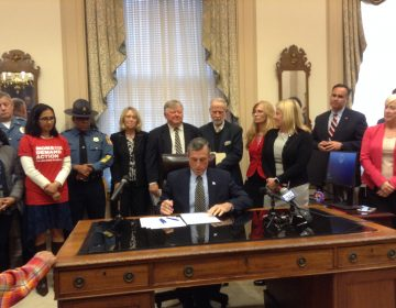 Delaware Gov. John Carney signs legislation Wednesday that raises the maximum sentence for the illegal purchase, transfer or possession of a firearm. (Zoe Read/WHYY)