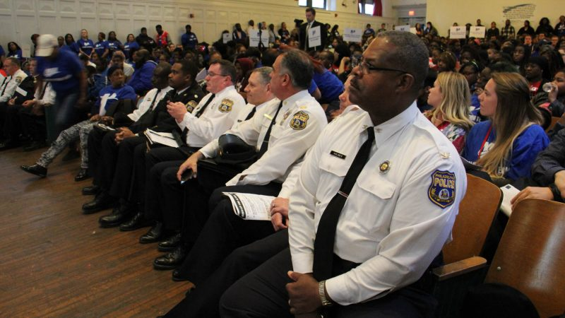 Representatives of the Philadelphia police department attend an assembly at Mastery Shoemaker Charter School focused on reducing gun violence. (Emma Lee/WHYY)