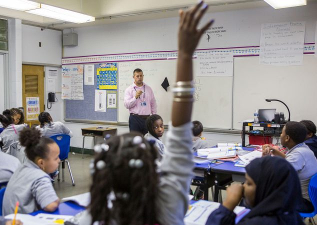 A student raises her hand in Higgins' math class. (Jessica Kourkounis/WHYY)
