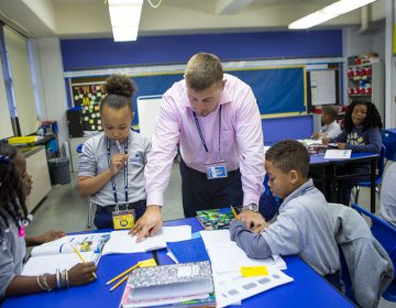 Nate Higgins works with students on math problems. (Jessica Kourkounis/WHYY)