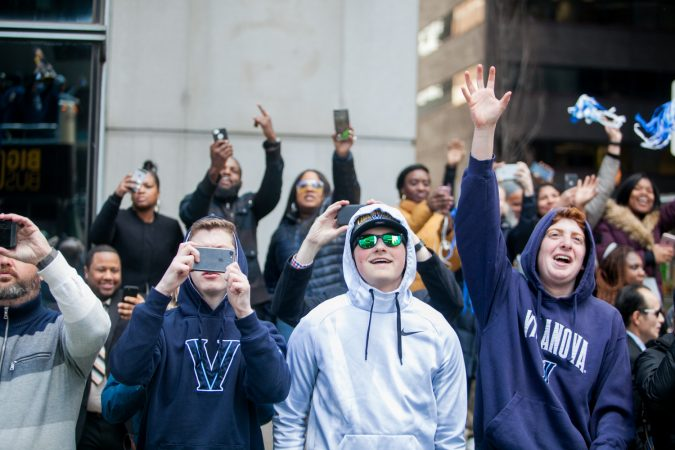Fans cheer for the NCAA Champion Villanova WIldcats basketball team as they ride down Market Street during their parade Thursday morning. (Brad Larrison for WHYY)
