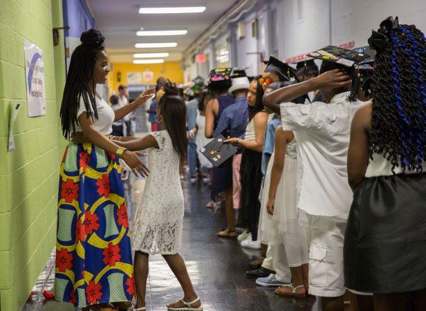 Shantel Shaw helps organize students before the graduation ceremony. (Lindsay Lazarski/WHYY)