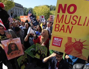 Demonstrators at a rally in Washington, D.C., protest the Trump administration's proposed travel ban, which goes before the Supreme Court Wednesday.