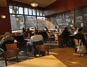 Customers sit in a Starbucks store in Seattle. (Ted S. Warren/AP)