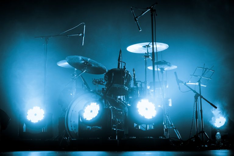 A kit of drums and a microphones on an empty stage in blue smoke before the concert
