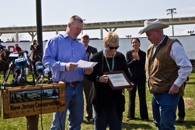 Pilesgrove Township Mayor Kevin Eachus presents Cowtown owners Betsy and Grant Harris with the preservation decree. (Kimberly Paynter/WHYY)