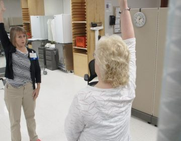 Physical therapist Ingrid Peele coaches Kim Brown through strengthening exercises to help her with her chronic pain, at the OSF Central Illinois Pain Center in Peoria. (Kyle Travers/WFYI)