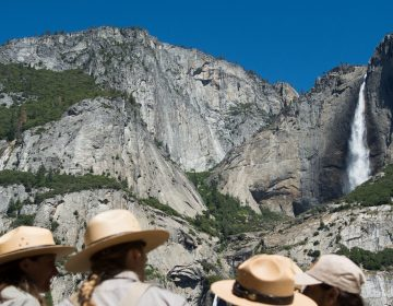 Park rangers meet in front of Yosemite Falls in 2016 in Yosemite National Park in California. Increased fees are expected to boost funding for park maintenance across the country. (David Calvert/Getty Images)