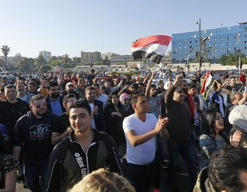 Syrians wave the national flag and portraits of President Bashar Assad as they gather at the Omayyad Square in Damascus on Saturday to condemn the U.S.-led airstrikes. (Louai Beshara/AFP/Getty Images)