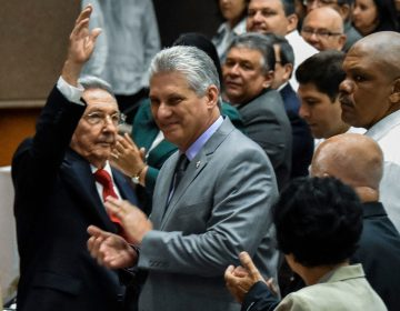 Cuban President Raul Castro waves to the room as First Vice President Miguel Diaz-Canel, Castro's handpicked successor, claps at the National Assembly session Wednesday in Havana. (STR/AFP/Getty Images)