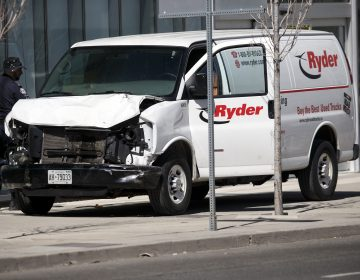 Police inspect a van suspected of being involved in a collision that killed at least 10 people and injured 15 others in Toronto on Monday. (Cole Burston/Getty Images)