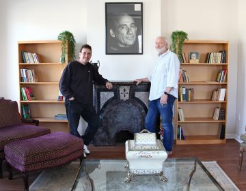 George Vallianos (left), president of the Nick Virgilio Haiku Association, and board member Henry Brann, stand beneath a portrait of the poet at the Nick Virgilio Writers House in Camden.