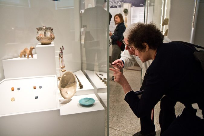 A Penn Museum curator and a visitor discuss the writing on a bowl in the Middle East Galleries. (Kimberly Paynter/WHYY)