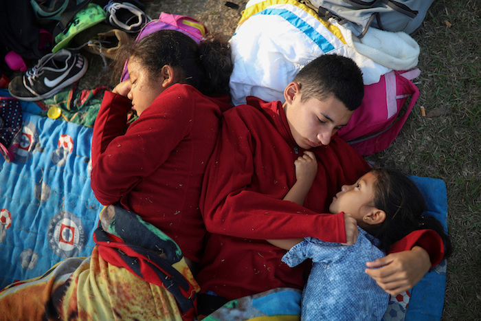 In this April 4, 2018 photo, the Zelaya siblings, from El Salvador, Nayeli, right, Anderson, center, and Daniela, huddle together on a soccer field, at the sports club where Central American migrants traveling with the annual