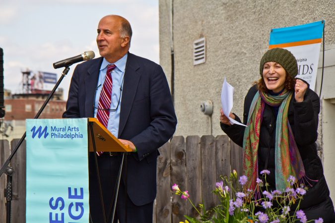 City Councilman Mark Squilla speaks at the dedication of a new mural on top of the Children's Crisis Treatment Center on Delaware Avenue in Philadelphia. Mural Arts' executive director Jane Golden celebrates. (Kimberly Paynter/WHYY)