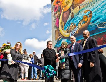 "(From left) Artist Meg Saligman, Antonio Valdes, executive director of the Children's Crisis Treatment Center, Jane Gold, Mural Arts executive director, Councilman Mark Squilla, and David T. Jones, DBHIDS commissioner, cut the ribbon on the ""Rippling Moon"" mural. (Kimberly Paynter/WHYY)"